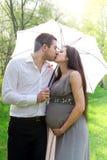 Het kussen van het paar onder de paraplu Royalty-vrije Stock Afbeeldingen