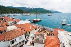 Het kustrood roofed stad, groene onderstellen royalty-vrije stock afbeeldingen