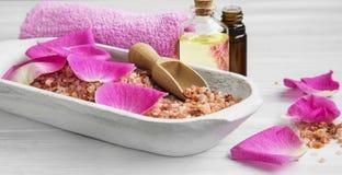 Het kuuroord die met roze badzout plaatsen, nam bloemblaadjes en lichaamsverzorgingolie B toe royalty-vrije stock foto's