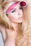 Het laagportret van een mooie blonde vrouw met groene ogen in roze hut, GLB Stock Foto's