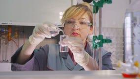 Het laboratorium met glaswerk en medewerker giet vloeistof in buis makend steekproefroze stock videobeelden