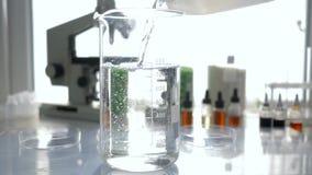 Het laboratoriumwerk, chemicus giet gefiltreerd water in glasclose-up in laboratorium in natuurlijk licht stock videobeelden