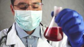 Het laboratoriumwerk, een mens arts houdt een reageerbuis, in een medisch masker en de glazen, neemt een analyse van een reageerb stock video