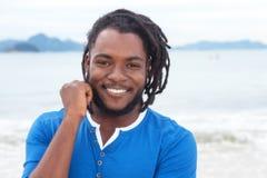 Het lachen Afrikaanse Amerikaanse kerel met dreadlocks bij strand Stock Foto's