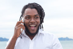 Het lachen Afrikaanse Amerikaanse kerel met dreadlocks en wit overhemd bij telefoon Royalty-vrije Stock Foto's