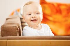 Het lachen babyzitting bij de bank Stock Fotografie