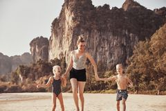 Het lachen de handen van de Moederholding met haar kinderen op een strand stock fotografie