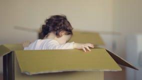 Het lachen de zitting van het kindmeisje in karton boxe in haar nieuw huis stock video