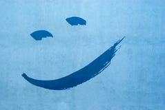 Het lachen gezicht van twee ogen en mond op een gepleisterde blauwe huismuur Royalty-vrije Stock Afbeelding