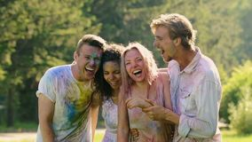 Het lachen gezichten van het doorweken van natte opgewekte vrienden die Holi-kleurenfestival vieren stock video
