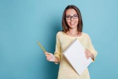 Het lachen het vrolijke mooie notitieboekje van de meisjesholding over blauwe achtergrond stock afbeeldingen