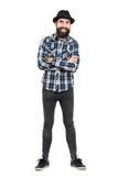 Het lachen hipster dragend fedora zwarte hoed met gekruiste wapens die camera bekijken stock foto