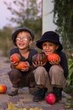 Het lachen jonge geitjes die met Halloween-pompoenen zitten Royalty-vrije Stock Afbeeldingen