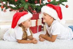 Het lachen jonge geitjes voor Kerstmisboom Stock Foto