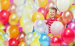 Het lachen jongen het spelen onder baloons stock afbeeldingen