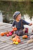Het lachen jongenszitting met Halloween-pompoenen Royalty-vrije Stock Foto