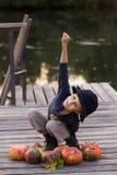Het lachen jongenszitting met pompoenen Royalty-vrije Stock Afbeeldingen