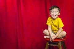 Het lachen Jongenszitting op Kruk voor Gordijn royalty-vrije stock foto