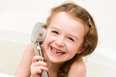 Het lachen meisje het spelen met douche in de badkamers Stock Afbeelding