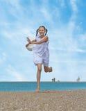 Het lachen meisjeslooppas langs het strand Stock Afbeeldingen