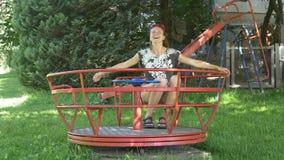 Het lachen vrouw het spinnen op carrousel in speelplaats stock footage