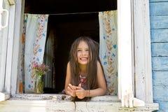 Het lachende blije meisje kijkt uit van het wijd open venster royalty-vrije stock foto's