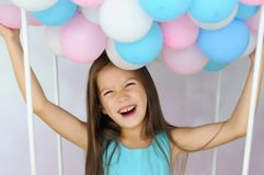 Het lachende meisje houdt vele gekleurde ballons met haar handen Royalty-vrije Stock Foto's