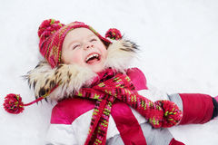 Het lachende meisje ligt op sneeuw Royalty-vrije Stock Afbeeldingen