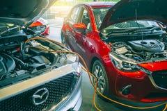 Het laden het merk Mazda 2 van de batterijauto Stock Afbeelding