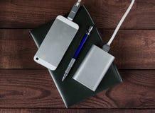 Het laden smartphone met grijze draagbare externe batterij op woode Stock Fotografie