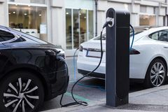 Het laden van moderne elektrische auto op de straat als toekomst van de automobielindustrie stock foto