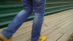 Het lage schot van mensenvoeten loopt op houten dek naast metaalomheining bij bouwwerf stock footage