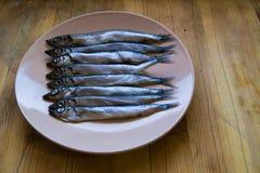 Het lage zijaanzicht van kleine zilveren vissen in een beige plaat op een houten lijst, sluit omhoog stock foto