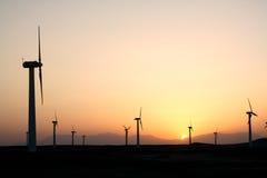 Het landbouwbedrijf van de wind na zonsondergang stock foto