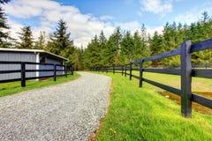Het landbouwbedrijf van het paard met weg, omheining en loods. royalty-vrije stock afbeelding
