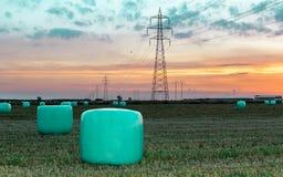 Het landbouwwerk op een gebied bij zonsondergang Materiaal voor foerage Film verpakkend systeem Ronde balen van voer voor landbou royalty-vrije stock afbeelding