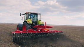 Het landbouwwerk op het gebied in de vroege lente De tractor gaat snel vooruit op het harrowing gebied weg, het land stock videobeelden