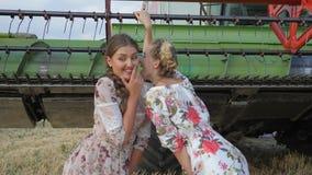 Het landelijke meisje in kleding het fluisteren Roddels van Meisje in oor op gebied dichtbij maaidorser stock videobeelden