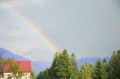 Het landschap van de berg Regenboog en zonnestralen over dorp stock foto