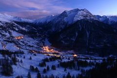 Het landschap van de de winterberg bij schemer met sneeuw en dorp stock afbeeldingen