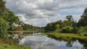 Het landschap van de lente Het schone water, blauwe hemel met witte wolken is weerspiegeld in de rivier stock footage