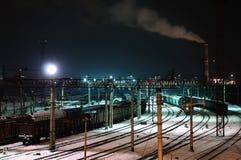 Het landschap van de nachtwinter van een station met treinen stock fotografie