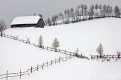 Het landschap van de winter met plattelandshuisje boven de heuvel royalty-vrije stock afbeeldingen