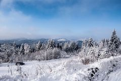 Het landschap van de de winterberg met sneeuw behandelde weg, bos, heuvels, sneeuw en blauwe hemel met wolken Stock Afbeelding