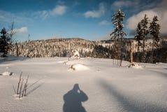Het landschap van de de winterberg met sneeuw, heuvels, weinig bomen, fotograafschaduw en blauwe hemel met wolken Royalty-vrije Stock Afbeeldingen