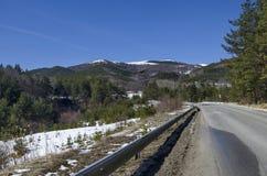 Het landschap van het de winterpanorama van pijnboom en vergankelijk bos met weg in Vitosha berg Royalty-vrije Stock Foto's