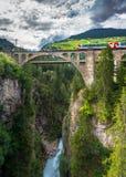 Het landschap van de de zomerberg met stroom, brug en rode trein stock afbeeldingen
