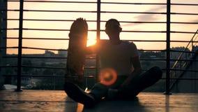 Het landschap van de zonsondergangstad met een jonge zitting op een trap die met zijn skateboard landen stock videobeelden