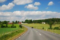 Het landschap van het land met een weg en landbouwbedrijven stock foto's
