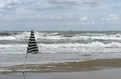 Het landschap van het strand met zonnescherm en golvende overzees Stock Fotografie